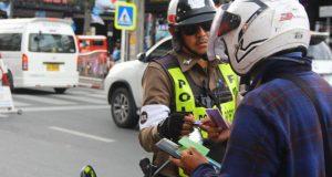 Phuket agente di polizia controlla la patente di guida di un motociclista